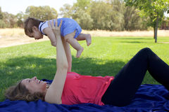 Mother and Newborn Baby. Having fun on a sunny day in the park Stock Image