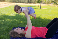 Mother and Newborn Baby. Having fun on a sunny day in the park Stock Images
