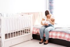 Mother with a newborn baby in her arms sitting in the children`s room on the bed stock image