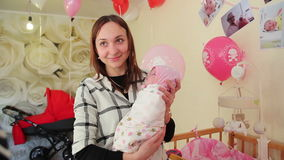 Mother with newborn baby is photographed on a background of balls and strollers. stock video