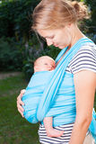 Mother with newborn baby in sling. Young mother carrying her little baby girl in blue sling Stock Images