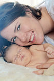 Mother and baby snuggle. A mother with her smiling face touching her newborn baby Royalty Free Stock Images