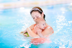 Mother and newborn baby son in swimming pool. Young mother and her newborn baby son having fun in a swimming pool stock photo