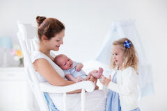 Mother with newborn baby and toddler daughter. Little sister hugging her newborn brother. Toddler kid meeting new sibling. Mother and new born baby boy relax in Royalty Free Stock Photo