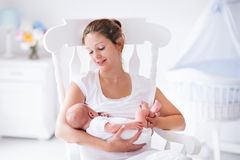 Mother and newborn baby in white nursery Stock Photo
