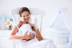 Mother and newborn baby in white nursery Royalty Free Stock Images
