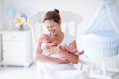 Mother and newborn baby in white nursery. Young mother holding her newborn child. Mom nursing baby. Woman and new born boy relax in a white bedroom with rocking stock photos