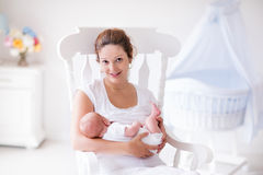 Mother and newborn baby in white nursery. Young mother holding her newborn child. Mom nursing baby. Woman and new born boy relax in a white bedroom with rocking stock image