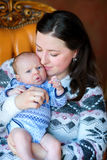 Mother with the newborn son. Mother carefully holds on hands of the newborn son, sits on a chair gently embraces the kid. Happy family. Motherhood Royalty Free Stock Images