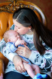 Mother with the newborn son. Mother carefully holds on hands of the newborn son, sits on a chair gently embraces and kisses the kid. Happy family. Motherhood Stock Photo