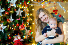 Mother with the newborn son. Mother gently embraces the newborn son, looks in the camera and smiles. On a background a set of bright fires. Waiting for a holiday stock photography