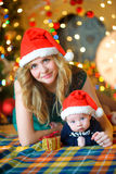 Mother with the newborn son. Mother together with the little son lie on a floor in Santa Claus`s caps, look in the camera and smile. On a background a set of Stock Photography