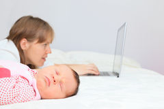 Mother with newborn working from home Royalty Free Stock Photos