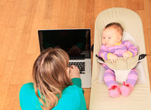 Mother with newborn working from home Royalty Free Stock Photography