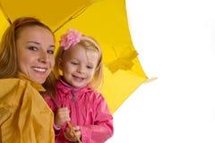 Mother och behandla som ett barn dottern under det gula paraplyet Arkivbild