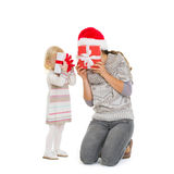 Mother och behandla som ett barn nederlag bak julgåvaaskar Arkivfoto