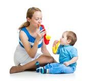 Mother och behandla som ett barn pojken som har gyckel med musikaliska toys Royaltyfri Bild