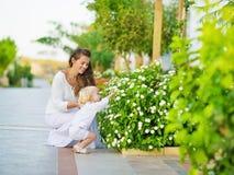 Mother och behandla som ett barn upptäcker grönsaklivstid utomhus Royaltyfri Fotografi