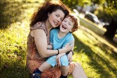 Mother och henne den rödhåriga sonen i parken Royaltyfri Bild