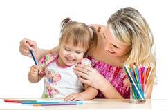Mother och henne roliga lekar för barnet med färgblyertspennor Arkivbilder