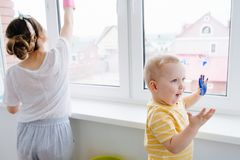 Mother Of A Toddler Boy Is Cleaning Plastic Window Door With Wet Cloth Royalty Free Stock Photo