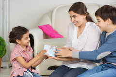 Mother and older brother presenting gift box to little sister on Royalty Free Stock Images