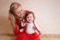 Mother with one year baby girl and red beads Royalty Free Stock Photos