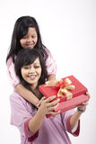 Mother opening a gift from her daughter. Mother and Daughter opening a Christmas gift isolated on white Stock Images