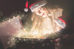 Mother opens magic box with gift for child. Christmas night! Stock Photography