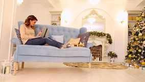 Mother orders gifts on Internet on computer for sons and pays plastic card, sitting on blue sofa in festively decorated. Elegant women is preparing surprise for stock footage