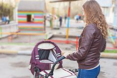Mother at outdoor shakes a baby carriage Royalty Free Stock Image