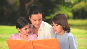 Mother outdoors with her children looking at a book Royalty Free Stock Photos