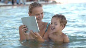 Mother with pad shows his son photo or video in stock footage