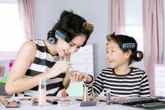 Mother painting nails her daughter Stock Photo