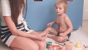 Mother painting a spider on her little boy. Professional shot in 4K resolution. 092. You can use it e.g. in your commercial video, business, education Stock Photos
