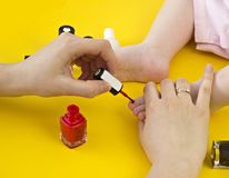 A mother paints her toenails with her little daughter, a yellow background, close-up cosmetics royalty free stock image