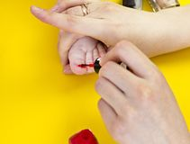 A mother paints her toenails with her little daughter, a yellow background, close-up cosmetics royalty free stock images