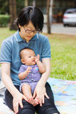 Mother parenting baby on park Royalty Free Stock Photography