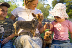 Mother on park bench with son and daughter (4-8) and dogs, close-up Royalty Free Stock Image
