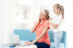 Mother is passionate about working on a laptop. Daughters do not have enough attention from mother. Woman feels tired, daughter tries to help her Royalty Free Stock Photos