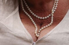 Mother of Pearl. Elderly woman's cleavage and pearl necklace royalty free stock image