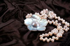 Mother of Pearl. Necklace on black satin Royalty Free Stock Photos