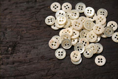 Mother-of-pearl buttons. On a dark brown wooden table Royalty Free Stock Image