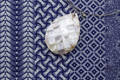 Mother of pearl pendant on indigo. Close up photo of mother of pearl pendant necklace on blue and white printed cloth Stock Images