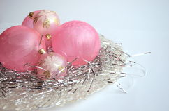 A mother of pearl plate with frosted pink Christmas ball ornaments on silver hair decoration with copy space Stock Images