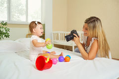 Mother  photographer photographing of her baby on camera. Stock Photography