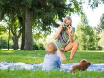Mother Photographing Baby Boy At Park Stock Images