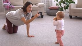 Mother photographing baby girl using mobile phone camera stock footage