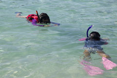 Mother photographing daughter while snorkeling Stock Photos