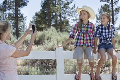 Mother photographing daughters through cell phone as they sit on fence at park Royalty Free Stock Photography